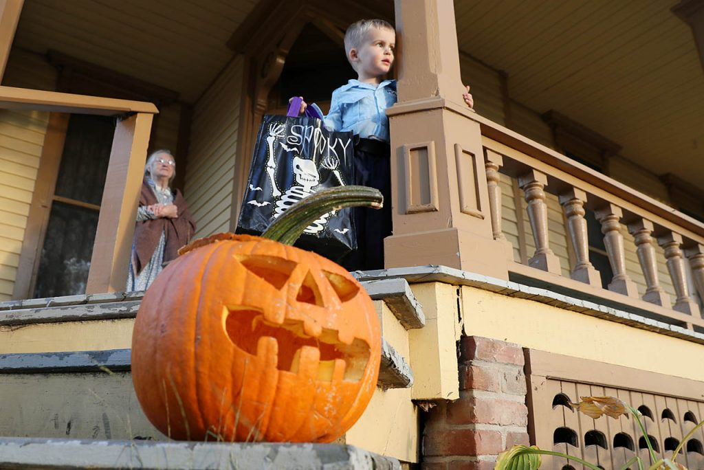 Evan Serbousek (dressed up as a policeman), stands on the porch of the former Lesher House located along Railroad Town during All Hallows Eve at Stuhr Museum Friday night.