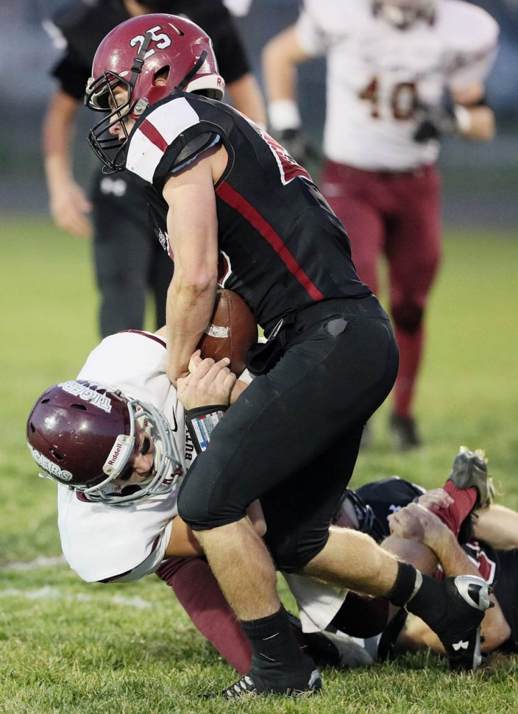 Heartland linebacker Austin Stuhr strips the ball from East Butler's Dalton Bohac, running it in for Heartland's first touchdown Wednesday night in Henderson.