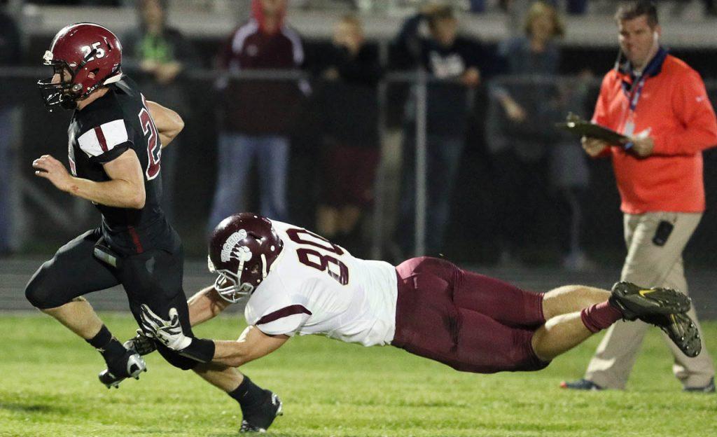 Heartland senior running back Austin Stuhr break a tackle by East Butler's Trevor Havlovic Wednesday night in Henderson.