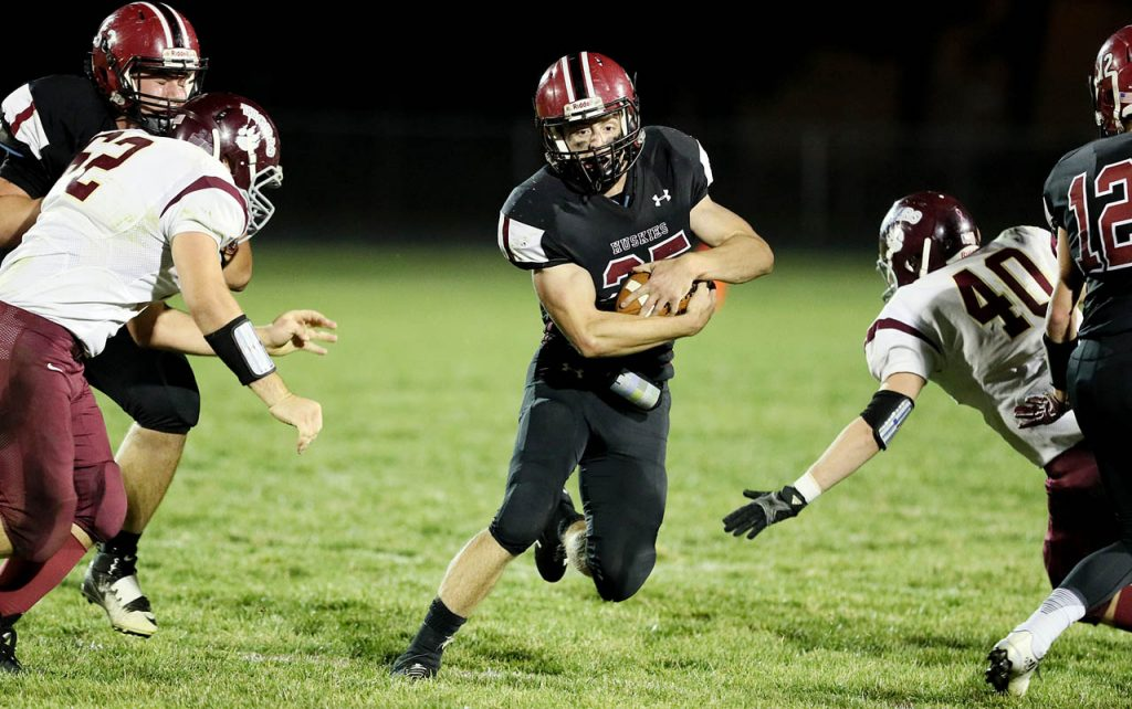 Heartland senior running back Austin Stuhr protects the ball with both hands running up field against East Butler Wednesday night in Henderson.