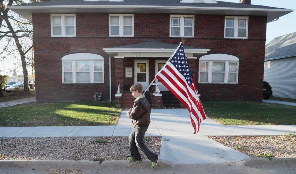 Brandon Woods with Cub Scouts pack 200 carries an American flag over his shoulder in route to the Veterans Recognition Parade in Hastings, Neb.
