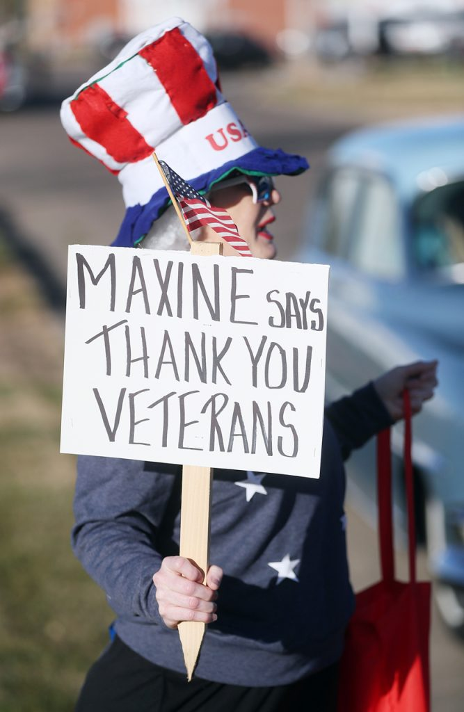 Maxine Jensen holds a sign while taking her place in line for the Veterans Recognition Parade in Hastings, Neb.