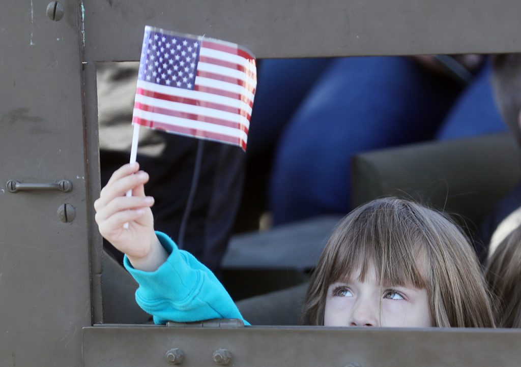 Tayla Allen holds a flag out of the window of one of several military vehicles driven during the Veterans Recognition Parade in Hastings, Neb.