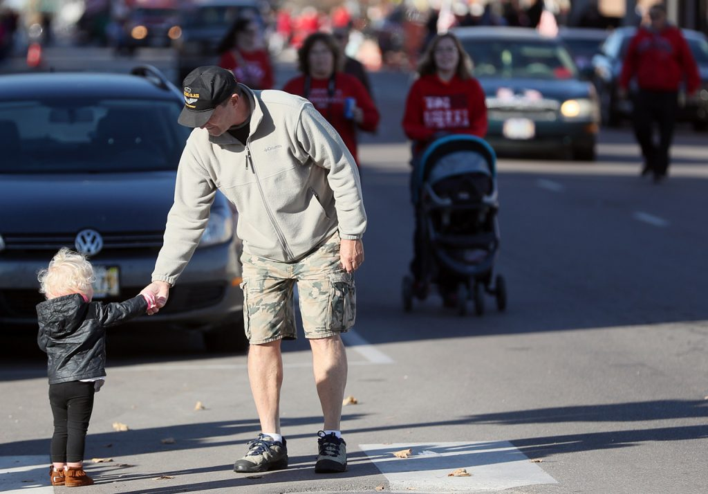 Veteran Mike Stutte hands out candy to children along Veterans Recognition Parade route in Hastings, Neb.