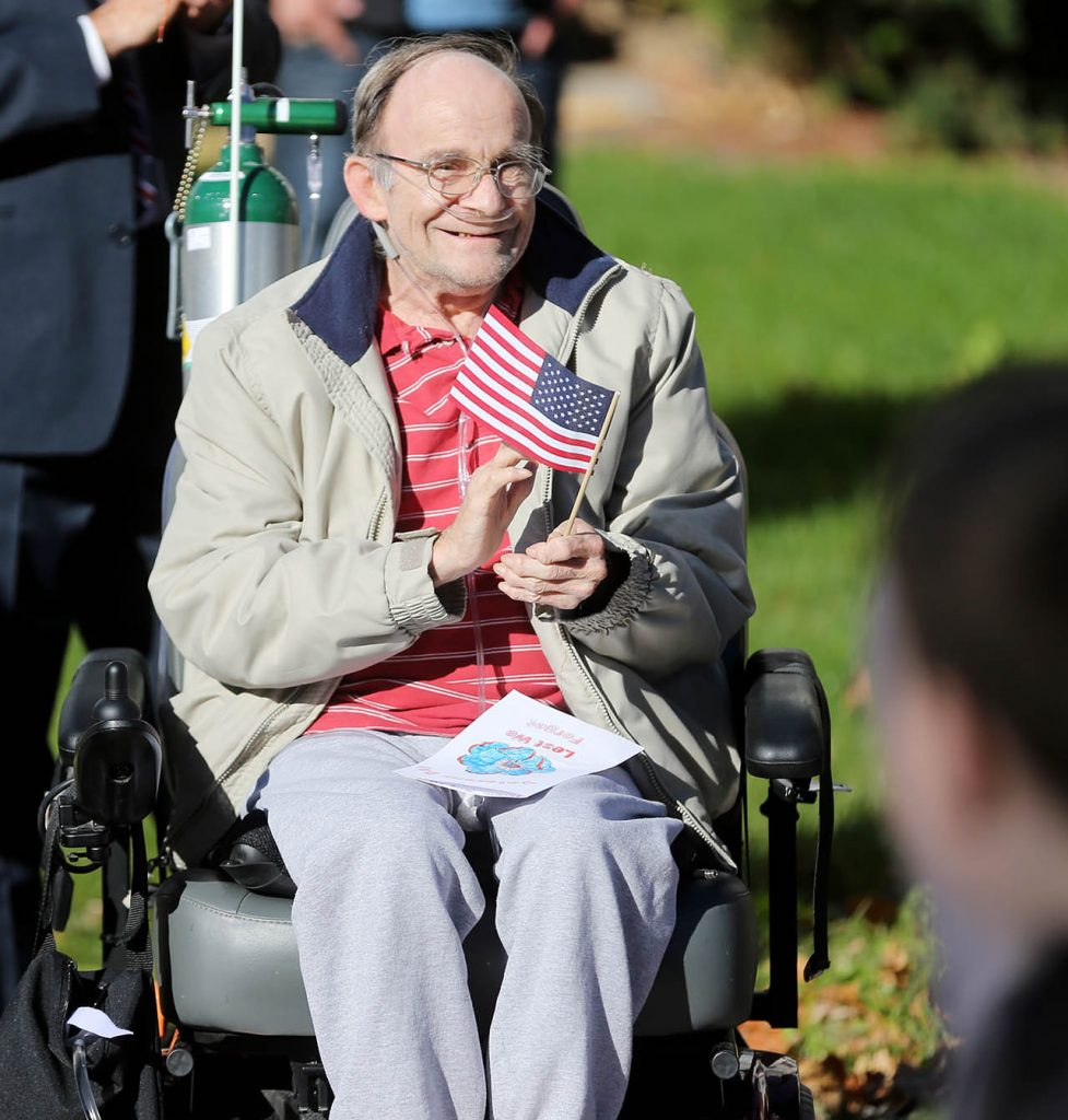 Naval Vietnam Veteran Bob LaBart claps while watching the Veterans Parade along Old Glory Road at the Grand Island Veterans Home.