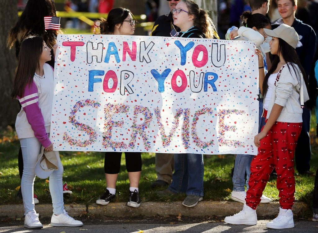 Makayla Aguilar and Aarliz Acosta hold a sign thanking veterans during a Veterans Parade at the Grand Island Veterans Home Wednesday. (Independent/Andrew Carpenean)