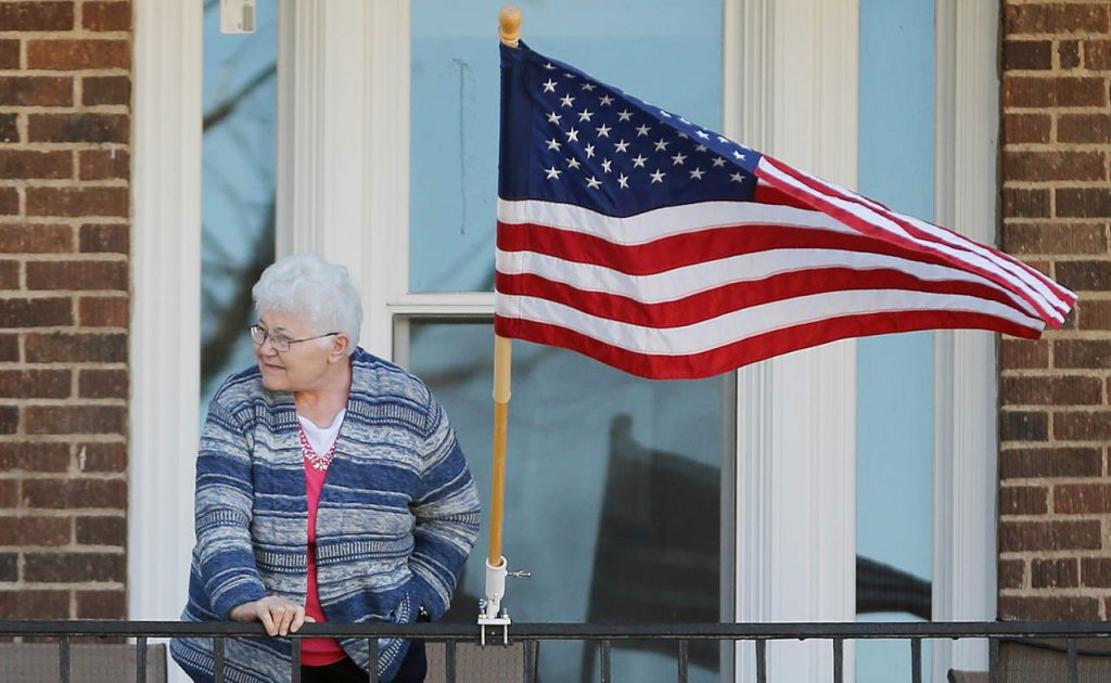 Trina Sanders, widow of veteran Bill Sanders stands next to a flag while watching the Veterans Parade at the Grand Island Veterans Home.