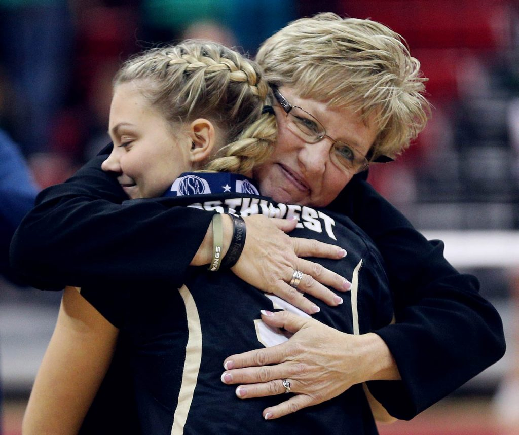 Grand Island Northwest head coach Diane Rouzee gives a hug to Mackenzie Hageman after receiving her second place state medal concluding the Class B NSAA State Championship against Omaha Skutt Catholic at the Devaney Sports Center Saturday. Skutt won in three straight sets.