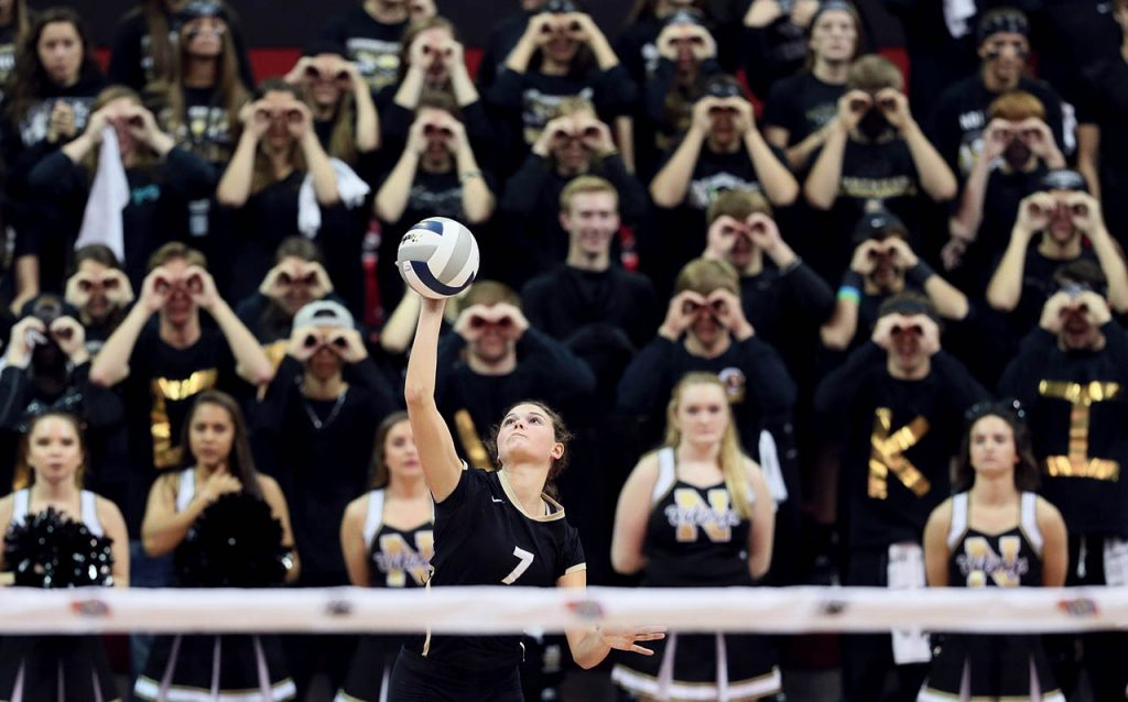 Grand Island Northwest Taylor Hageman serves with Vikings fans making kaleidoscope eyes behind her during the Class B NSAA State Championship against Omaha Skutt Catholic at the Devaney Sports Center.