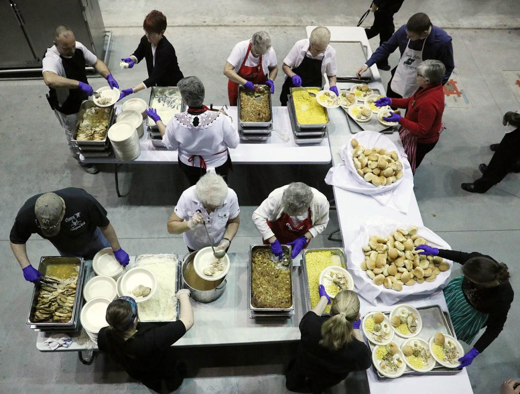 Servers prepare plates for up to 1,300 people during the 35th annual Five Points Bank Golden Club members Christmas party at the Heartland Events Center Thursday. (Independent/Andrew Carpenean)