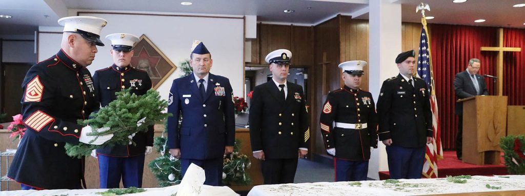 1st Sgt. Jose Carpio prepares to place a wreath in honor of Merchant Marines during a Wreaths across America ceremony at Grand Island Veterans Home, All Faiths Chapel Saturday. Alex Willford, Veterans Home administrator, introduces Carpio at the podium. (Independent/Andrew Carpenean)