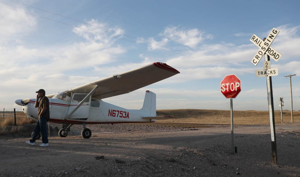 Mark Wickard of Scottsbluff, Neb. talks on his cell phone while standing next to his Cessna, in which, he made an emergency landing on Bluff Center Rd. northwest of Cairo, Neb. Wednesday. The plane rolled back down a hill on a dirt road stopping several feet from railroad tracks.