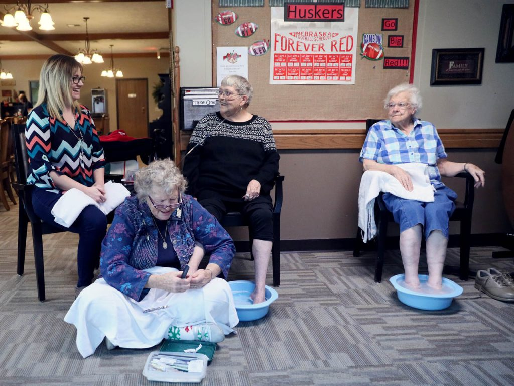 Claire Schmidt gives a pedicure to Lebensraum Assisted Living resident Charlene Rathjen while activities director Nicole Reyes, left, and Phyllis Runge, right, sit nearby.
