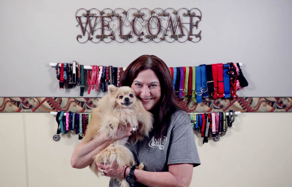 Tracie Pfeifle, a volunteer at the Central Nebraska Humane Society, holds a Pomeranian available for adoption inside the intake room.