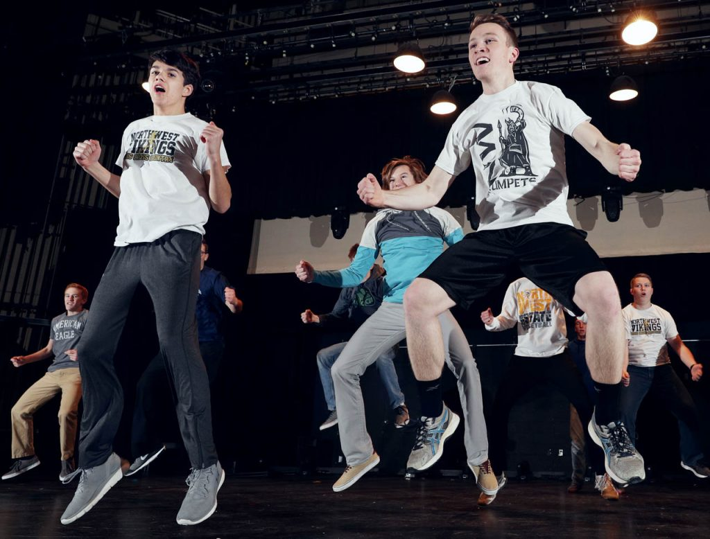 Tyson Burt and Christopher Rosenlund jump simultaneously with other Grand Island Northwest High School classmates while rehearsing. The Doods is an all-male show choir.