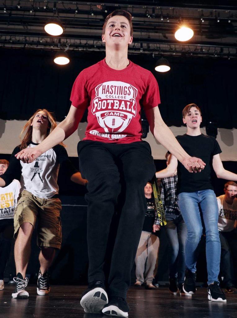 Jason Bachle, center, performs on stage in the Grand Island Northwest High School auditorium with other classmates. The Doods is an all-male show choir.