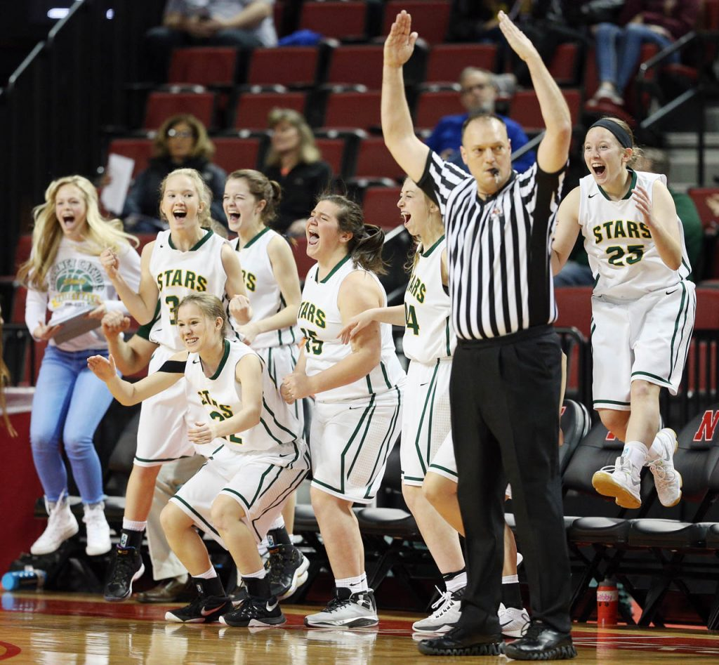 The Kearney Catholic Stars team bench celebrates a teammates three-pointer during a Class C1 semifinal State Girls Basketball game at Pinnacle Bank Arena Friday. Kearney Catholic won 54-39.