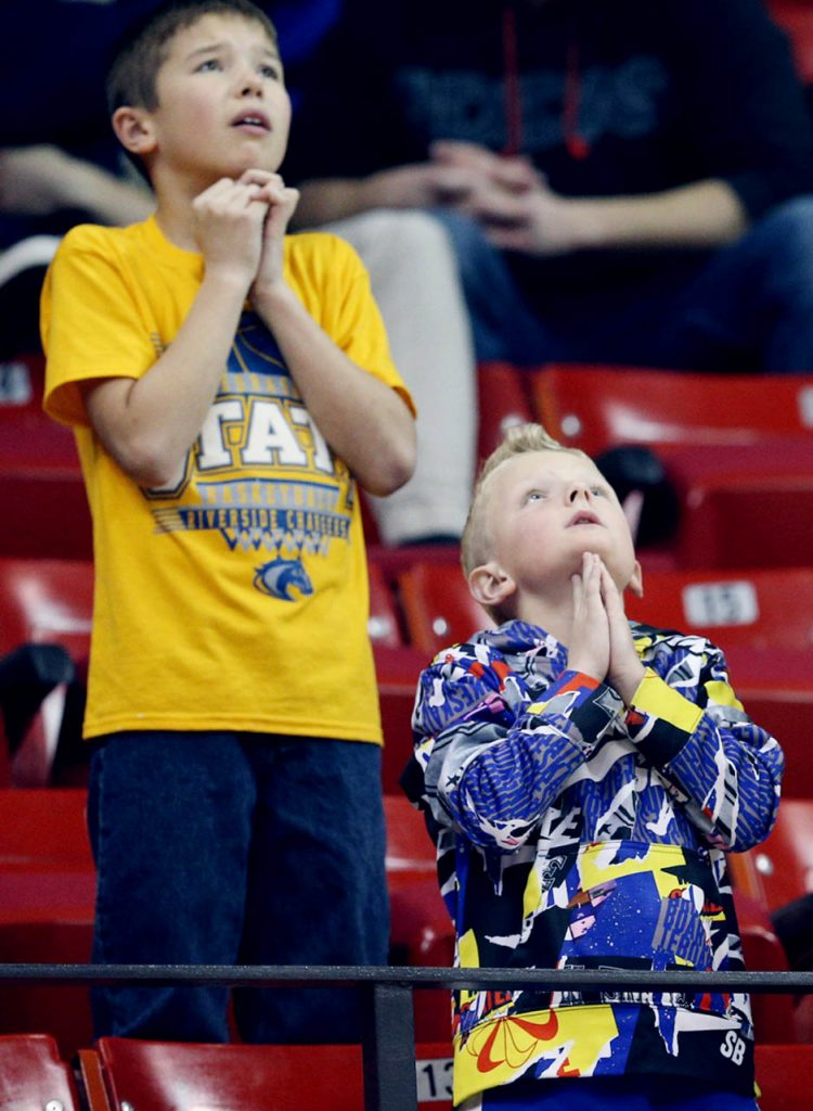 Riverside fans seek divine intervention late in the fourth quarter against Mullen during the Nebraska State Boys Basketball Championships at the Bob Devaney Sports Center Friday. Riverside won 54-52.