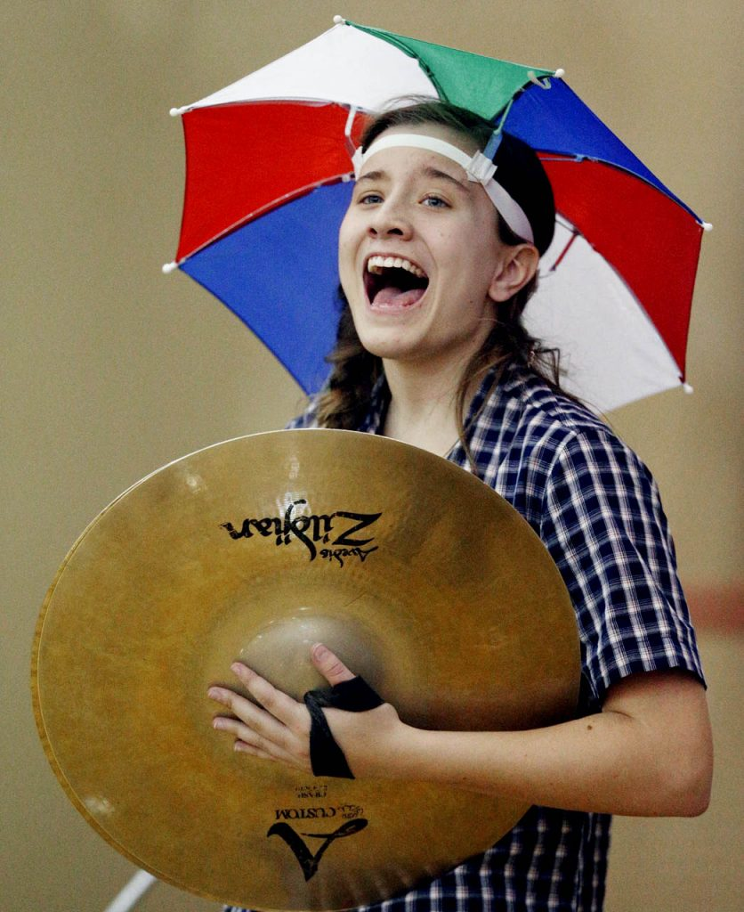 Sophia Schroeder, a sophomore at Ravenna High School cheers while holding symbols and donning a multicolor umbrella hat during the Ravenna vs. North Platte game at the Nebraska State Girls Championships at Lincoln North Star High School Thursday. Ravenna won 57-49.