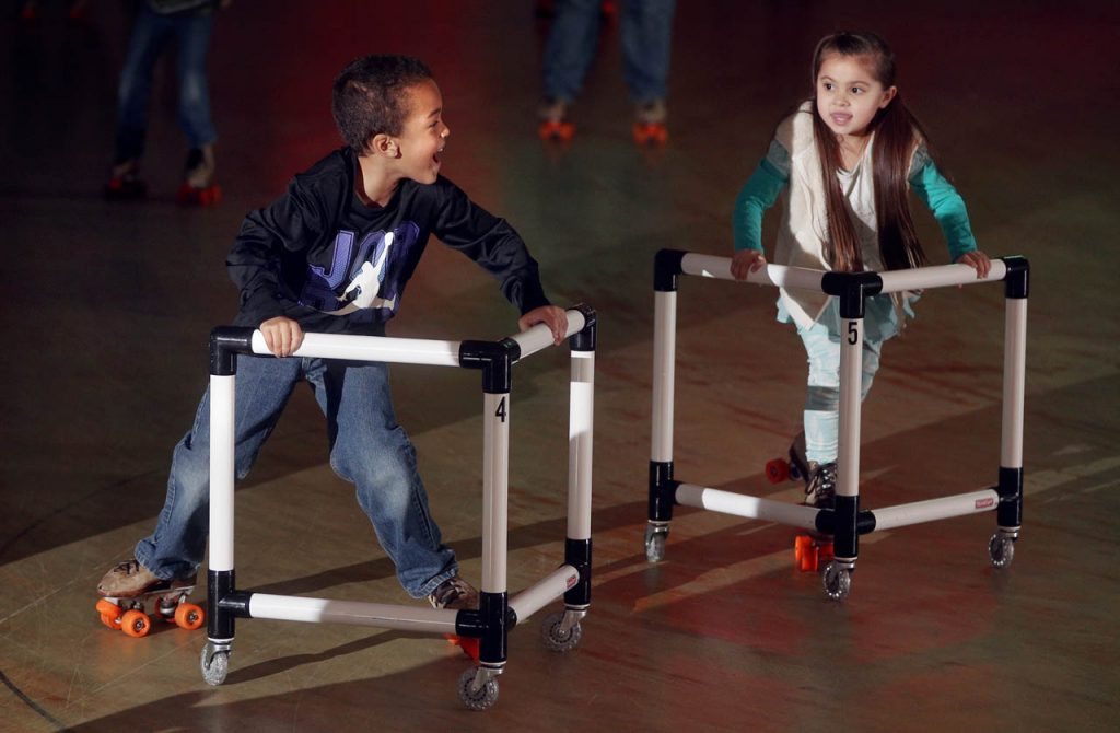 Malachi Halte and Angelica Stienike use skate walkers to brace themselves while refining their skating skills at Skate Island.