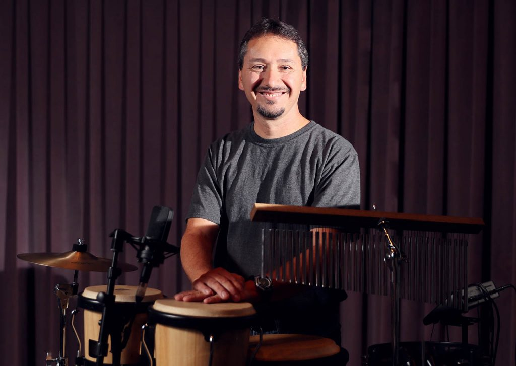 Tony Casarez, a custodian at Grand Island Evangelical Free Church, stands at a drum set he plays with the worship team during Sunday services.
