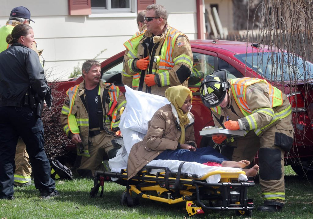The driver of a Ford Focus sits on a gurney as Grand Island public safety officials respond to the scene of an accident in which a car struck a house at 707 Joehnck Rd. Wednesday.
