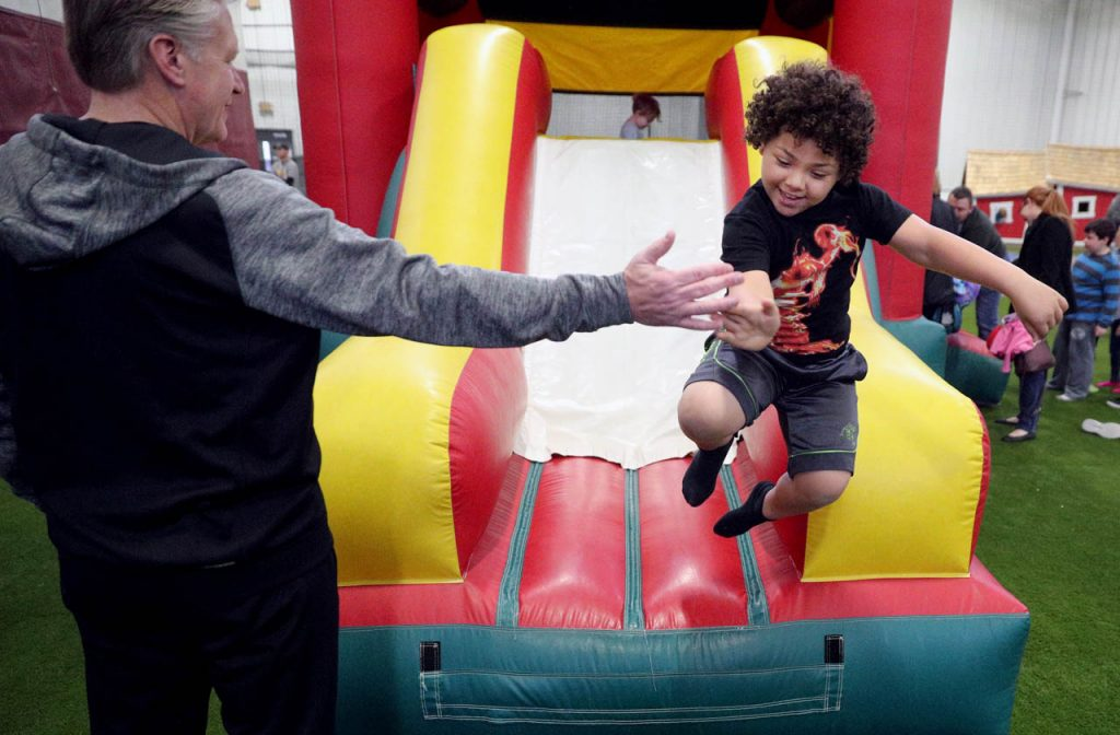 Peace Lutheran Church member Dan Thayer, left, gives a high five to Jaron Harwell as he slides out of a bounce house during an Easter egg hunt and activities Saturday at the Grand Island Parks & Recreation Community Fieldhouse.