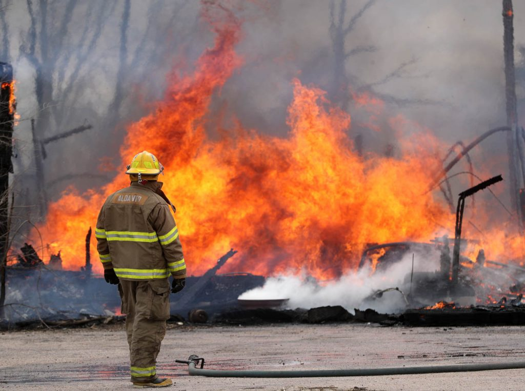 A fully engulfed structure burns to the ground as an Alva volunteer firefighter watches after containing the north perimeter of the inferno at the intersection of Alda and Stolley Park Roads Tuesday.