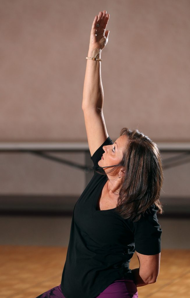 "Bonnie Bellamy looks upward with a reverse warrior pose. ""It opens the chest and heart as an offering up to God"" said Bellamy after teaching a yoga class inside the Jubilee Center at Blessed Sacrament Catholic Church."