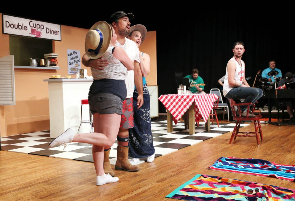 Prudie Cupp (Kelsey Helget) and Rhetta Cupp (Jana Thompson) swoon over L.M. (Michael Walters) as lifeguard Eddie (Tyler Jacobs) watches during a dress rehearsal of Pump Boys and Dinettes musical comedy put on by Grand Island Little Theatre at College Park Auditorium. The production includes a live band.
