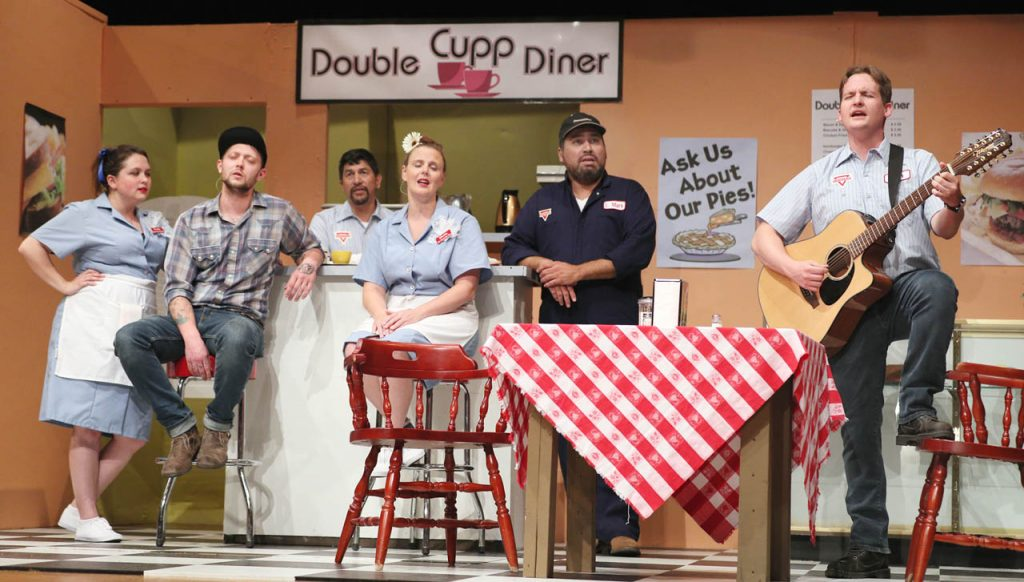 Prudie Cupp (Kelsey Helget) Eddie (Tyler Jacobs) Jackson (Greg Sanchez) Rhetta Cupp (Jana Thompson) L.M. (Michael Walters) sing on Jim's (Mike Bockoven) lead on acoustic guitar at the Double Cupp Diner during a dress rehearsal of Pump Boys and Dinettes musical comedy put on by Grand Island Little Theatre at College Park Auditorium.