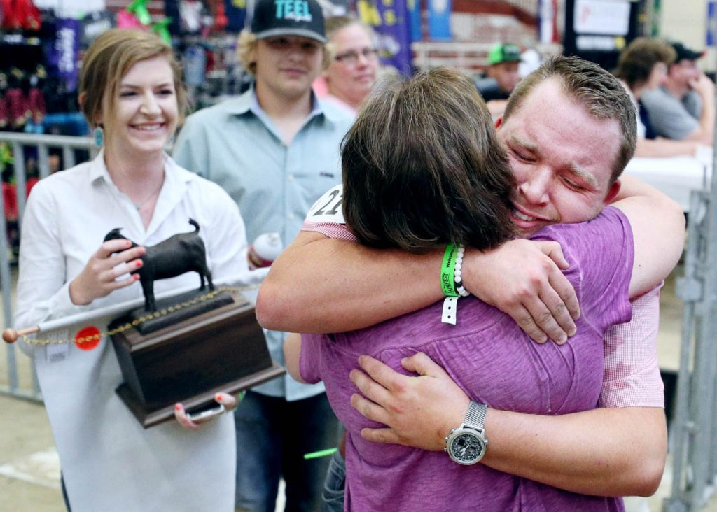 Noah Teel of Stillwater, Okla. gives an emotional embrace to his mother Barbie after becoming a National Champion in the Yearling Percentage Boer Doe during the American Boer Goat Association National Show Wednesday at Five Points Bank Arena. Family friend Emma Rethans, left, holds Teel's trophy.