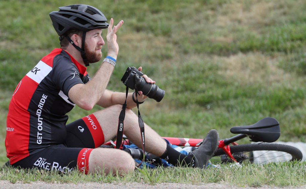 Ben Fischer of Lincoln, tour photographer, waves to other cyclists between taking pictures during the 2017 Tour de Nebraska on Hwy. 11 Wednesday.