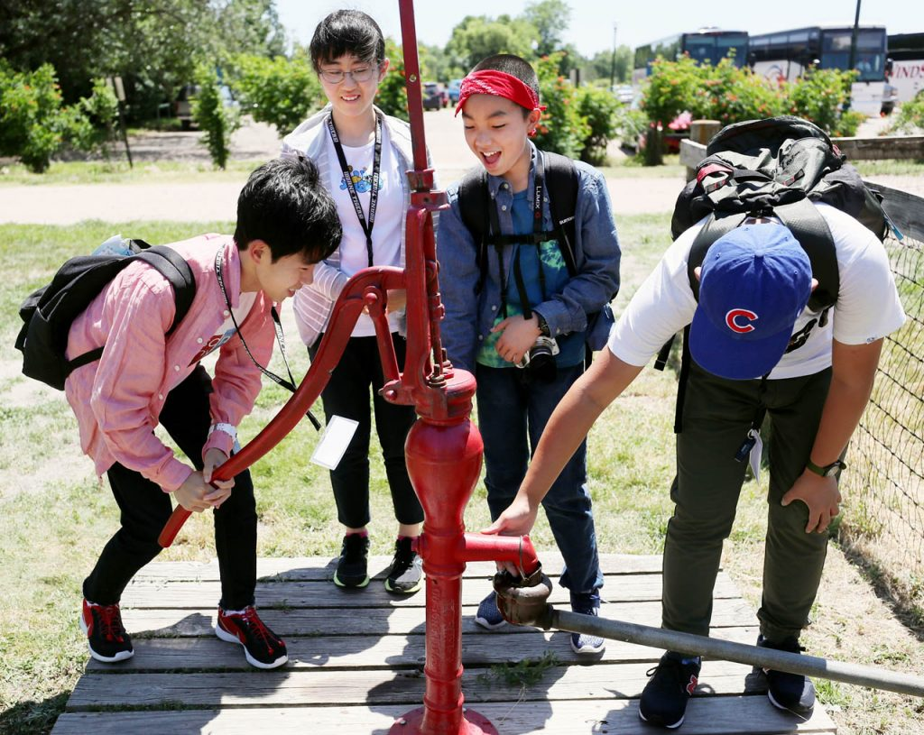 Sho Aoyama, left, pumps water up from a water well as other ninth-graders watch as Senshu Academy students from Tokyo, Japan take a tour of the 1897 Railroad Town Wednesday at Stuhr Museum.
