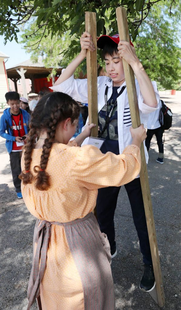 Senshu Academy's Natsuki Ono, right, learns to walk on stilts with some help with Delaney Tracy as students from Tokyo, Japan take a tour of the 1897 Railroad Town at Stuhr Museum Wednesday.