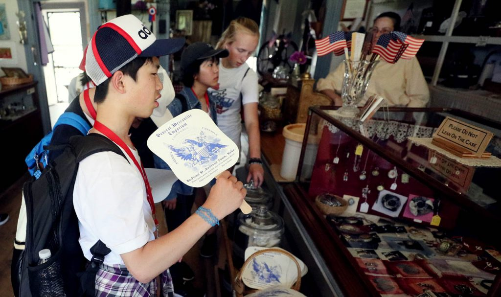 Tsubasa Hosaka fans himself while looking at items inside the Mercantile store in Railroad Town at Stuhr Museum.