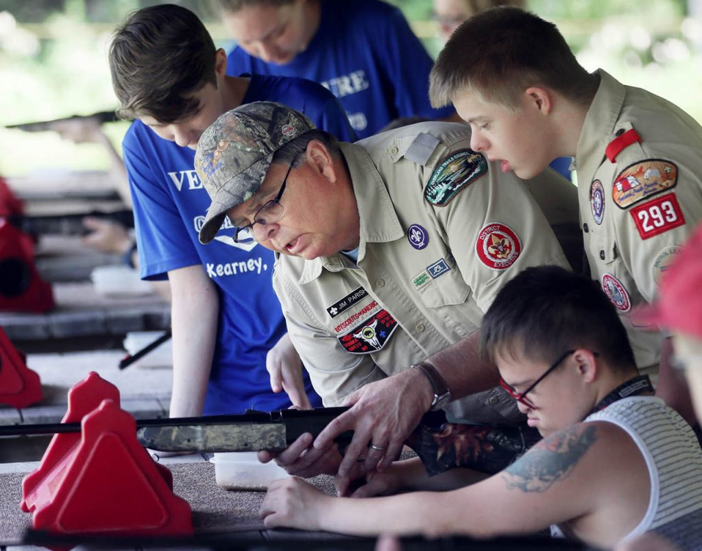 Jim Parish, district executive with Boy Scouts Troop 316 in North Platte, fixes a jam on a BB gun shot by Daniel Kluska at the Camp Augustine Robert Freeman rifle range Saturday. A new Boy Scout troop for the developmentally disabled took part in outdoor activities. Parish's son Zach, right, looks over his shoulder.
