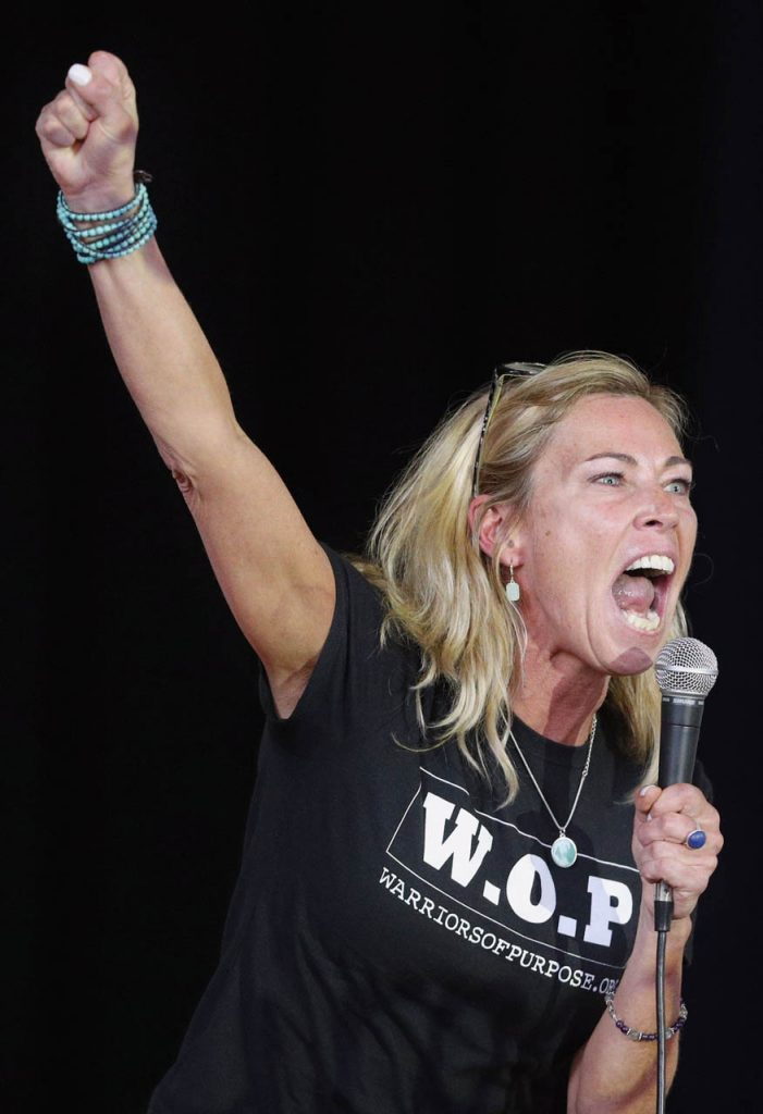 Reality star Trish Hegarty who appeared on Survivor clenches her fist in the air while giving a motivational speech to raise awareness of substance abuse and mental health education inside the French Chapel at Hastings College Thursday. Warriors of Purpose made their4th stop of the day in Hastings, Neb.