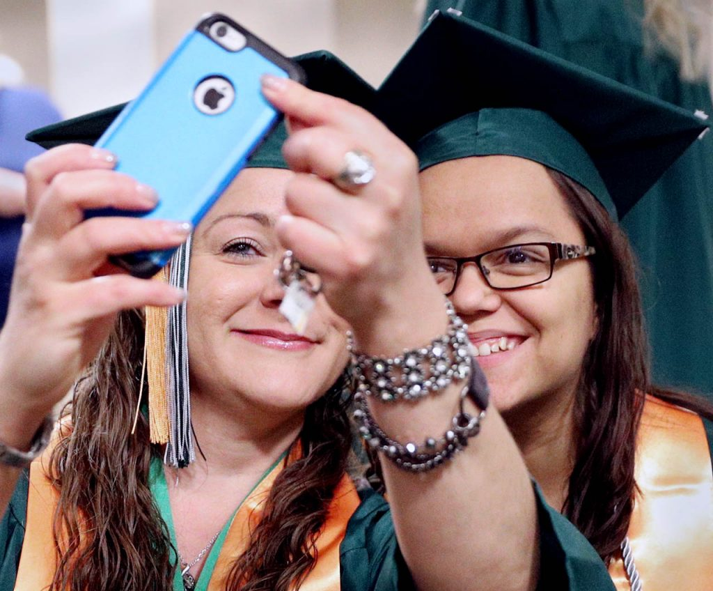 Angela Balcom of Riverdale, left, snaps a selfie with her classmate Mira Bettendorf of Norfolk prior to the Central Community College graduation ceremony Saturday at the Heartland Events Center. Both graduates received an Associate of Applied Science Degrees as Occupational Therapy Assistants.