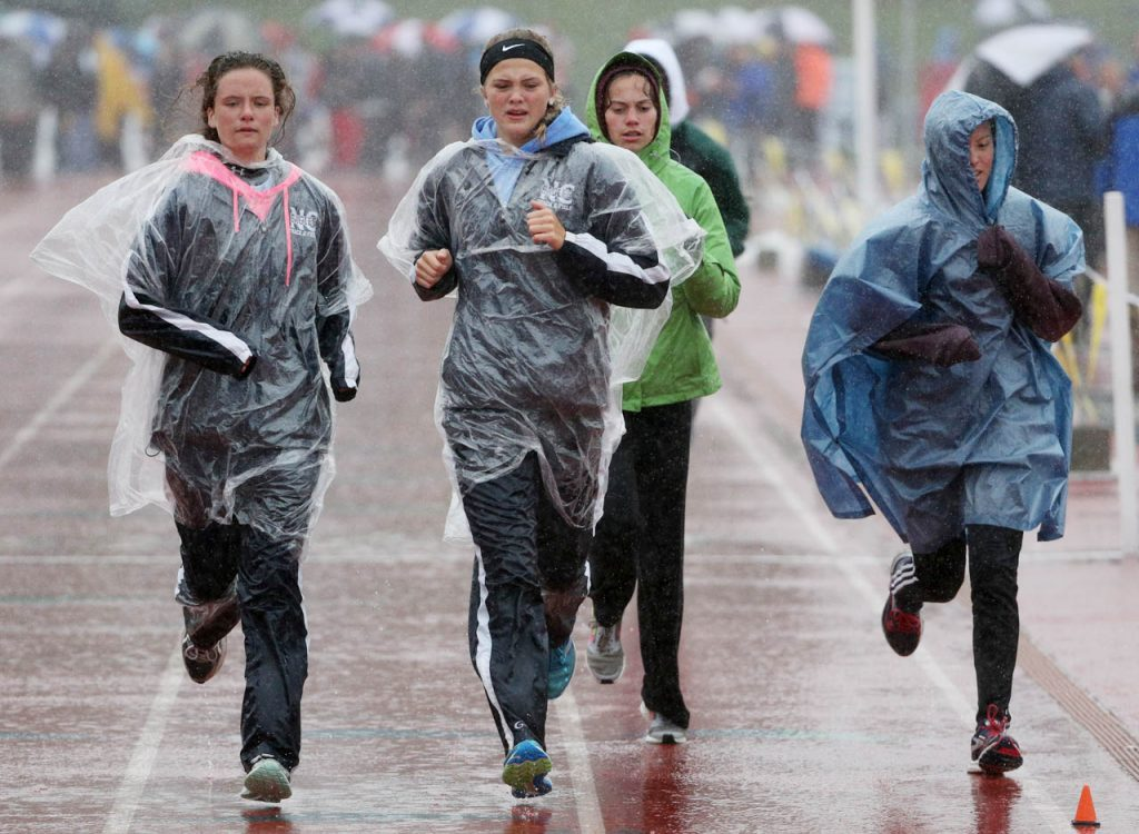 Athletes wear parkas while warming up during the Nebraska State Track & Field Meet at Omaha Burke Stadium.