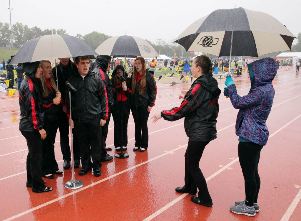 Kelli Flesch conducts members of the Sutherland High School Octet as they sing the National Anthem under golf umbrellas in a pouring rain to start the Nebraska State Track & Field Meet at Omaha Burke Stadium.