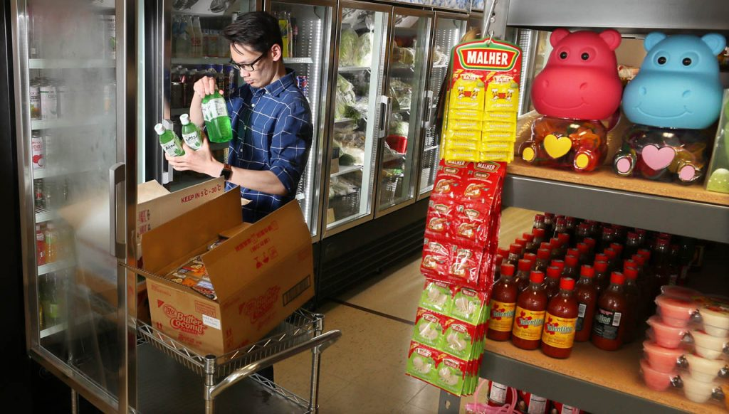 Liu Lichen stocks a refrigerator with an aloe vera drink at 88 Oriental Market at 1512 S. Locust.