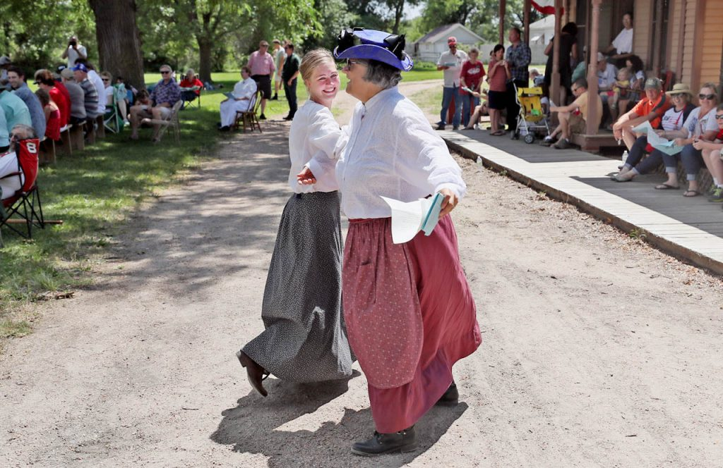 Nakia Wilkerson and Elizabeth Kuta dance arm-in-arm while the Railroad Town Silver Cornet Band plays during a 1897 Fourth of July Celebration in Railroad Town at Stuhr Museum.