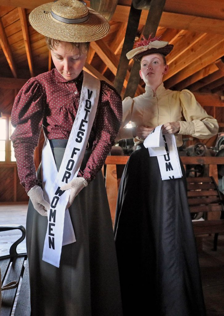 Kelsey Patton and Alyssa Smith put on sashes while preparing for a parade inside the Henry Glade Roller Mills during a 1897 Fourth of July Celebration in Railroad Town at Stuhr Museum.