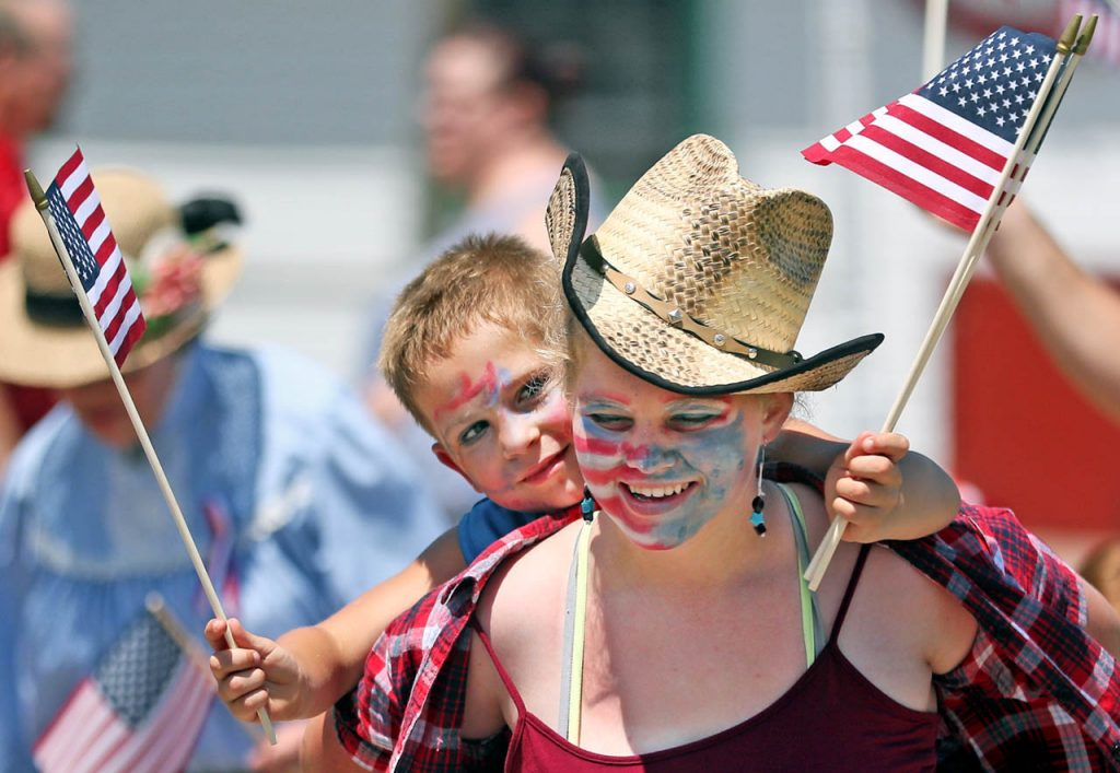 Simon Kramer looks over the shoulder of Julie Walz while getting a piggy back ride along a parade route on Front St. during a 1897 Fourth of July Celebration in Railroad Town at Stuhr Museum.