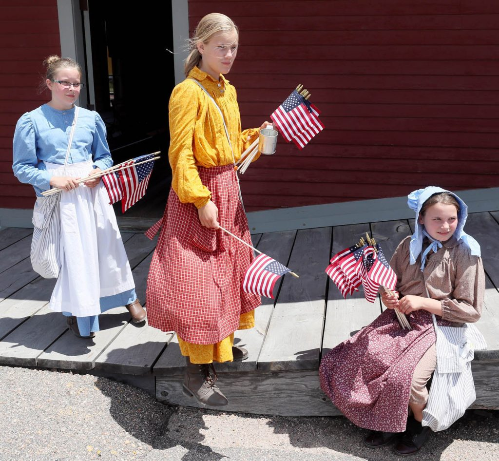 Anna Zentz, Summer Parnell and Callee Carman hand out American flags during a 1897 Fourth of July Celebration in Railroad Town at Stuhr Museum.
