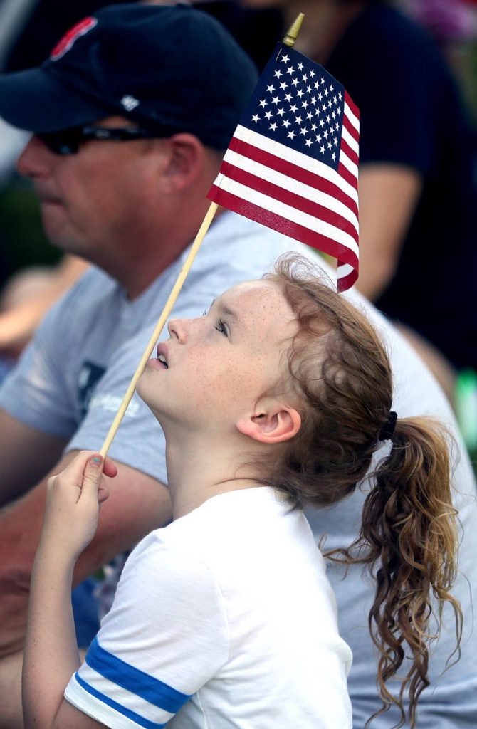 Taryn Brewer looks up at a flag she's holding during a 1897 Fourth of July Celebration in Railroad Town at Stuhr Museum.