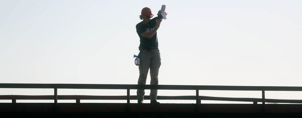Amy Jones, administrative director for Prairie Plains Resource Institute, snaps a picture with her cell phone while standing on a bridge.