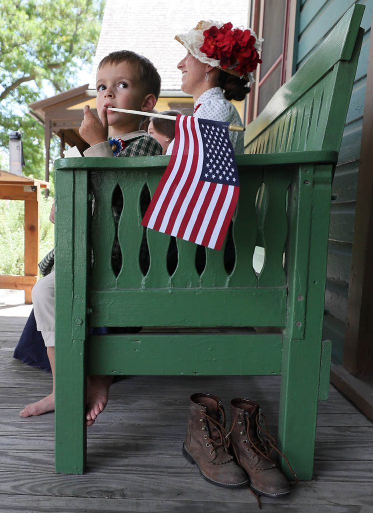 Aric Hoagland of Hastings took off his boots after walking in a parade while sitting with his mother Amy in front of the travelers home during a 1897 Fourth of July Celebration in Railroad Town at Stuhr Museum.
