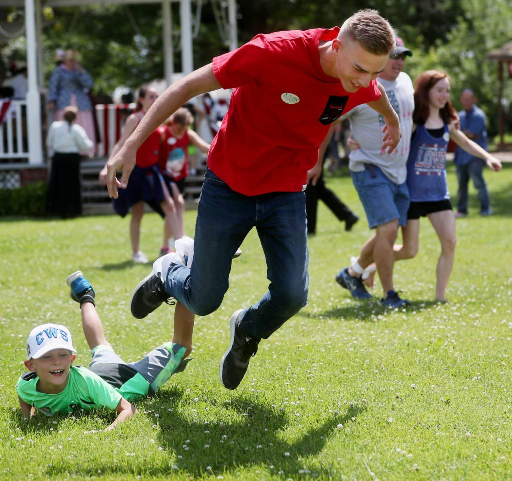 A pair of participants fall down while competing in a three-legged race during a 1897 Fourth of July Celebration in Railroad Town at Stuhr Museum.